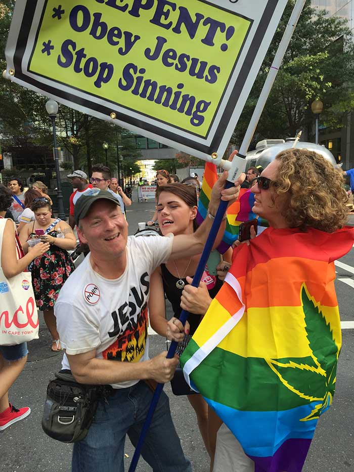 women-taking-sign-from-buddy-fisher-at-pride