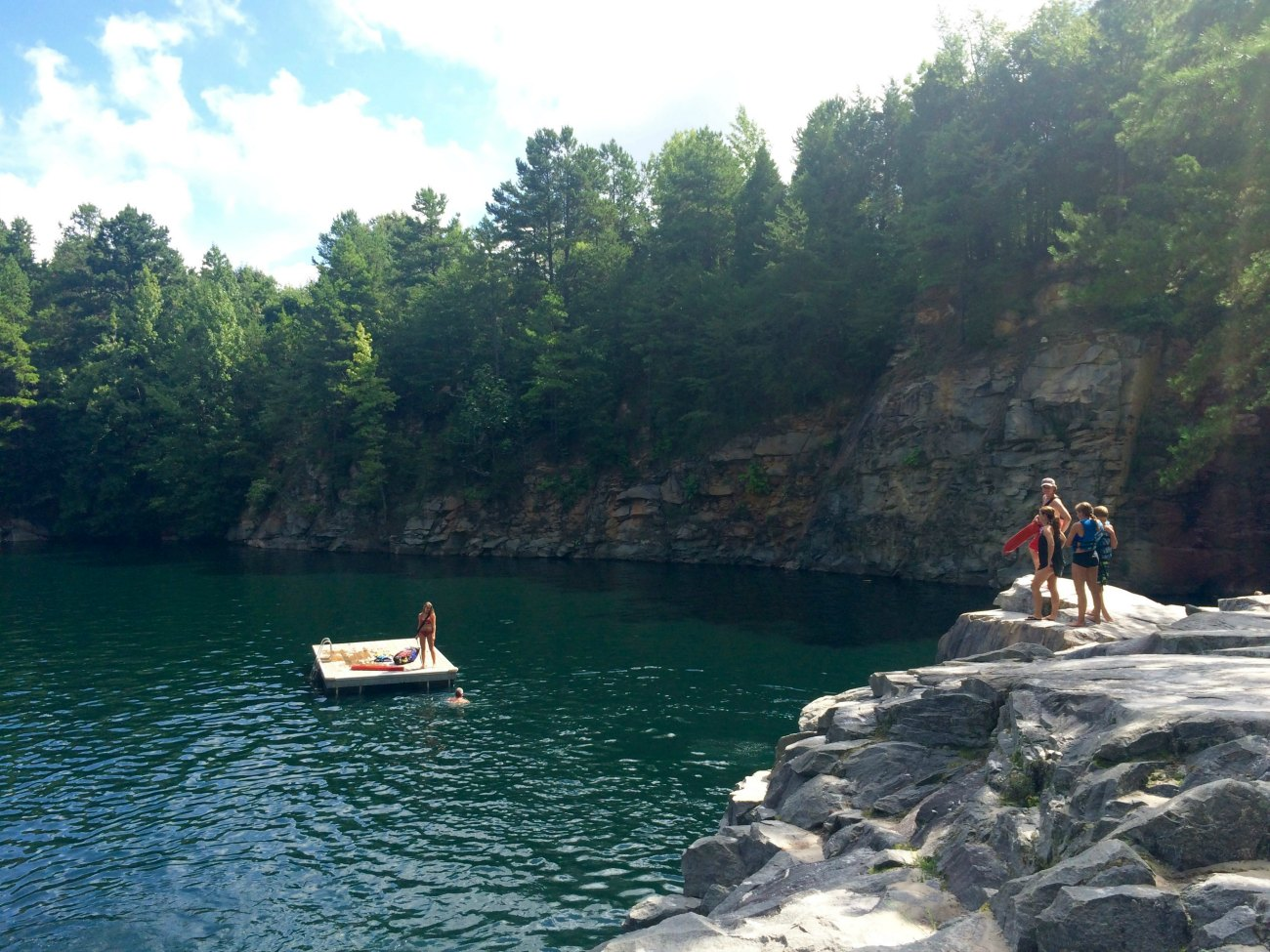 Plunge off rocky cliffs into blue-green water at The Quarry
