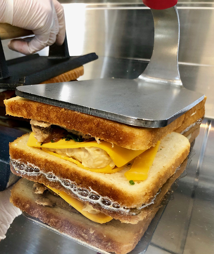 making grilled cheese at papi queso charlotte