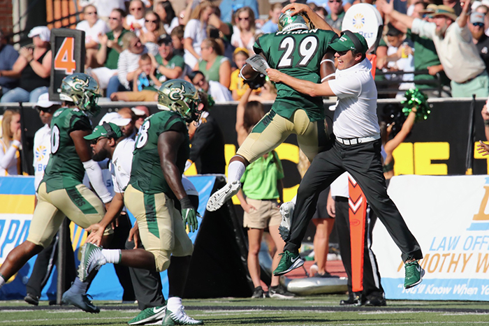 UNC Charlotte football coach Will Healy celebrates with the team